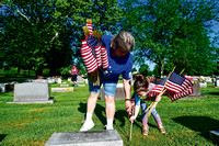 Volunteers place flags on the graves of veterans